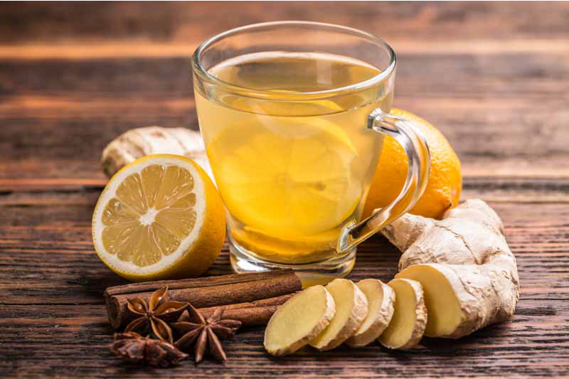 Image - A glass cup of lemon tea is picture on a wooden surface and is surrounded by ginger root, lemon, anise and cinnamon.
