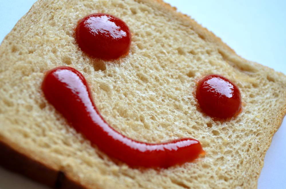 Image. Tomato sauce makes smiley face on a piece of bread.
