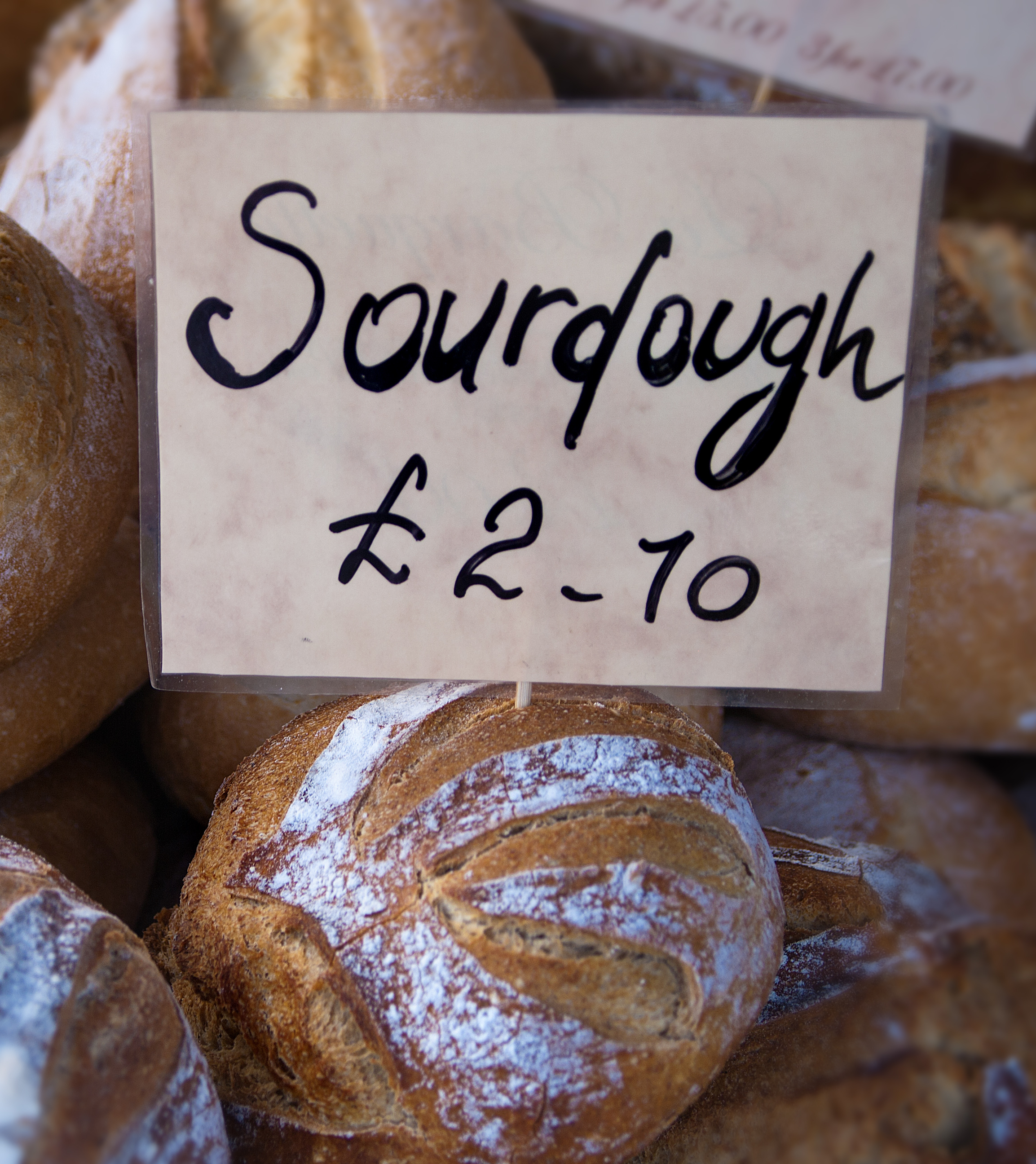 Image of a Sourdough label. Hand written on mottled, plastic coated paper, mounted on a stick and stuck into a sourdough loaf that is part of a display of sourdough loafs.