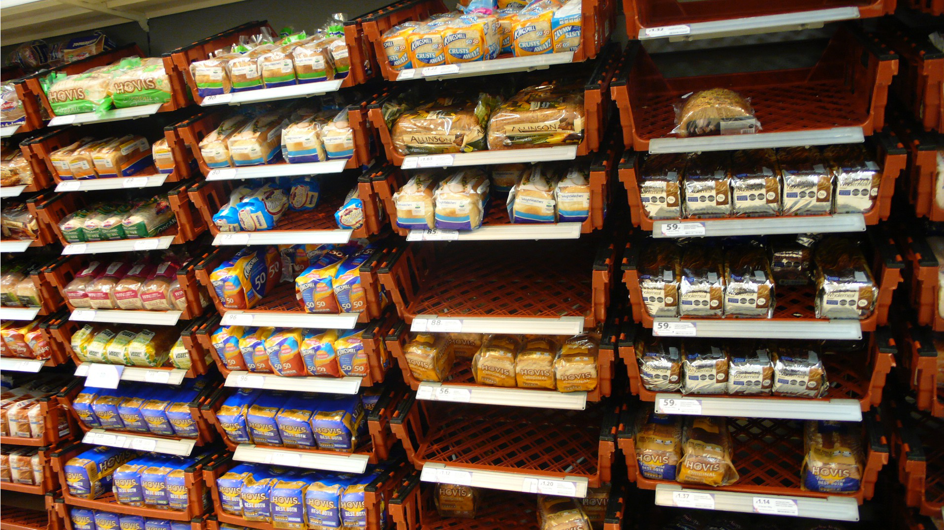 Image of supermarket bread, mostly white. The bread is displayed in bread trays, stacked at least 8 high along the wall.